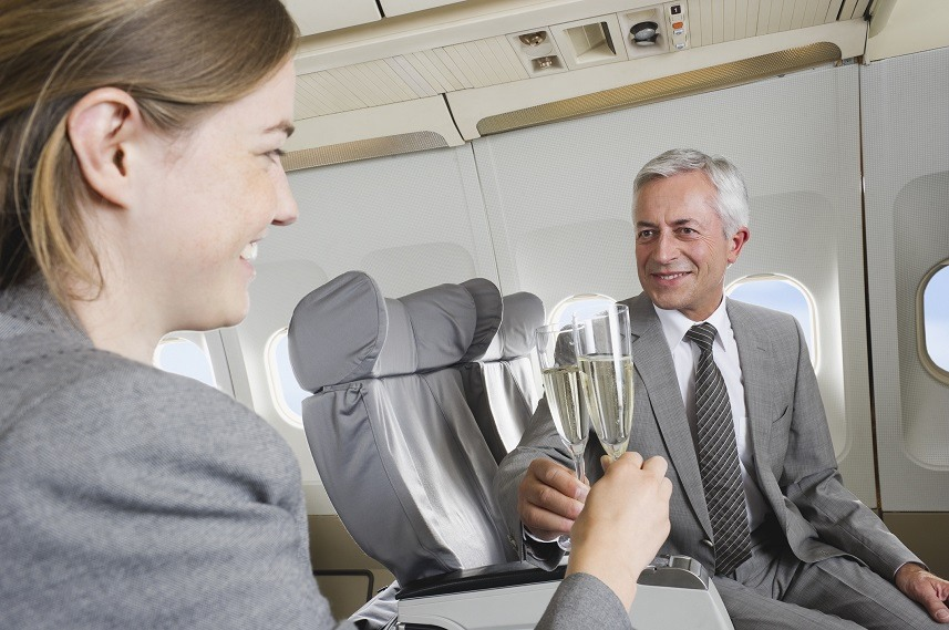 toasting with champagne business class airplane cabin