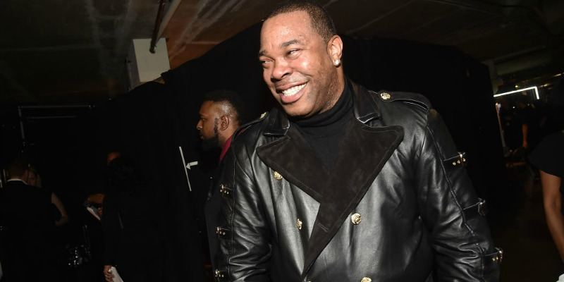 Busta Rhymes is smiling wearing an all black outfit.