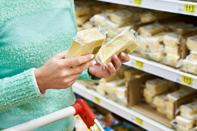 customer chooses the cheese in the store