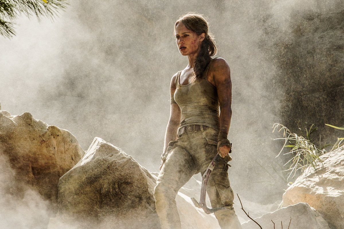 Alicia Vikander's Lara Croft stands on some boulders in Tomb Raider