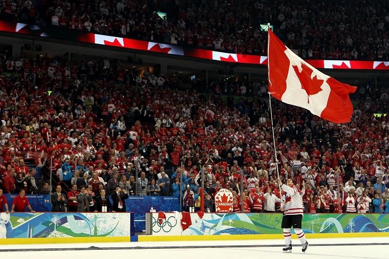 Sidney Crosby of Canada waves a national flag.