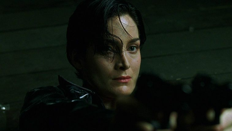 Carrie-Anne Moss looking into the camera in a dark room in The Matrix