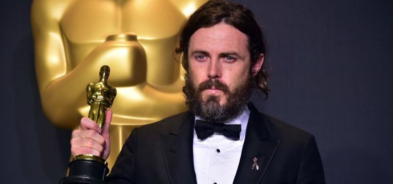 Casey Affleck is holding up his Oscar in a tux.