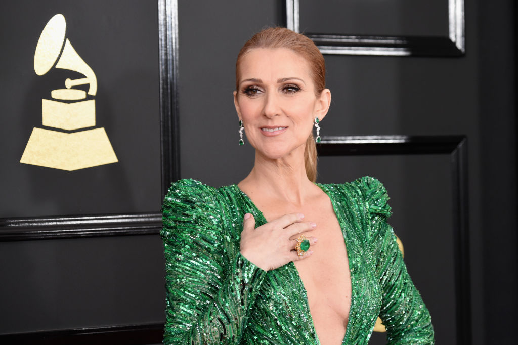 Singer Celine Dion is posing in a green dress on the red carpet.