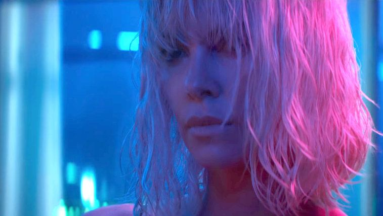 Charlize Theron in a blue room with pink light on her blond hair in Atomic Blonde