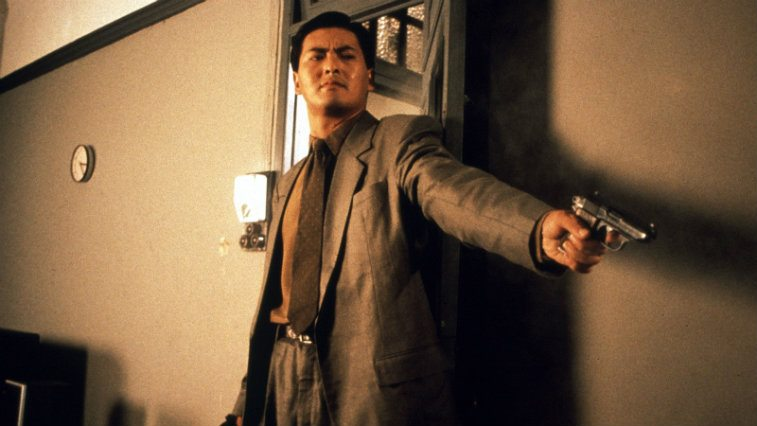 Chow Yun-Fat standing in a room pointing a gun in The Killer