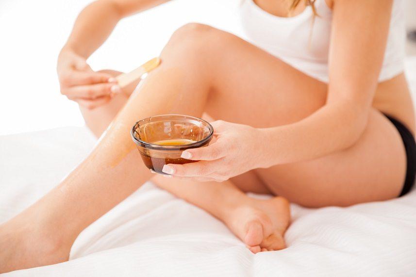 Woman putting wax on legs