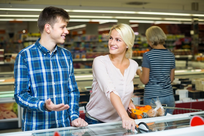 Couple looking at frozen food in grocery store.