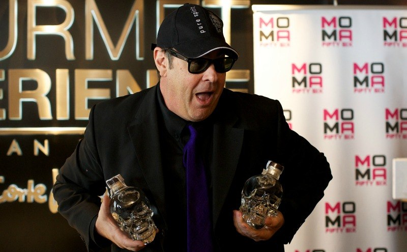 Dan Aykroyd holding two bottles of Crystal Head Vodka