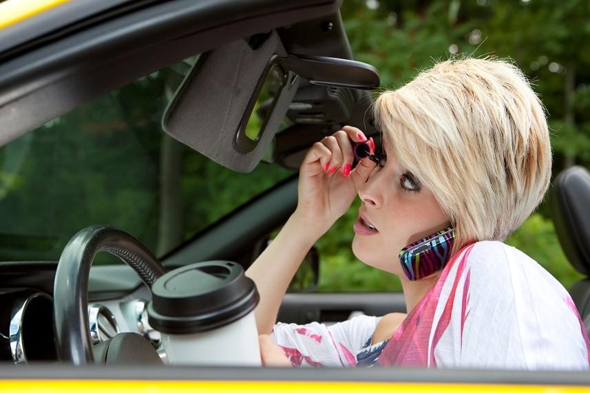 Woman applying makeup in the car