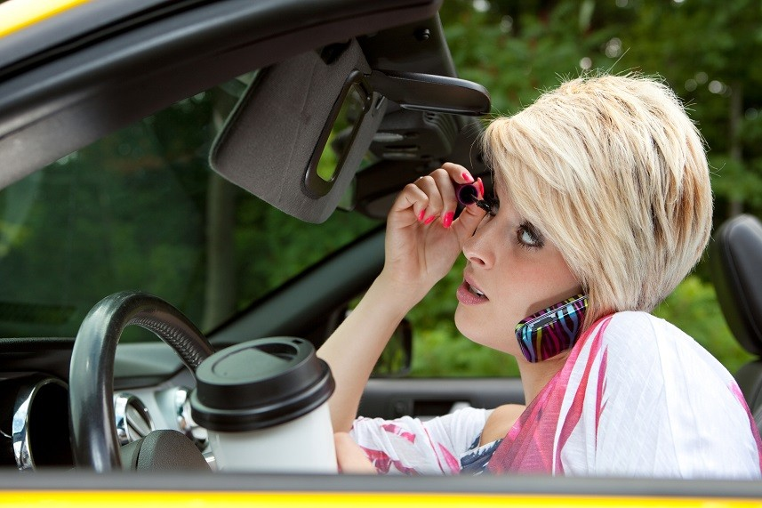 Young woman applying makeup in car