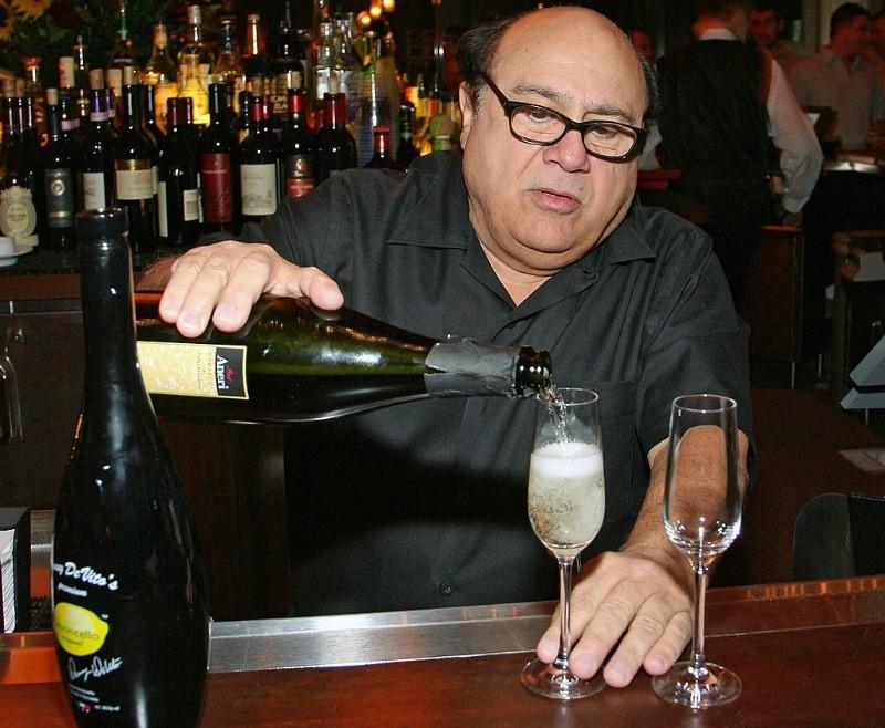 Danny DeVito poor a glass of Danny DeVito's Premium Limoncello