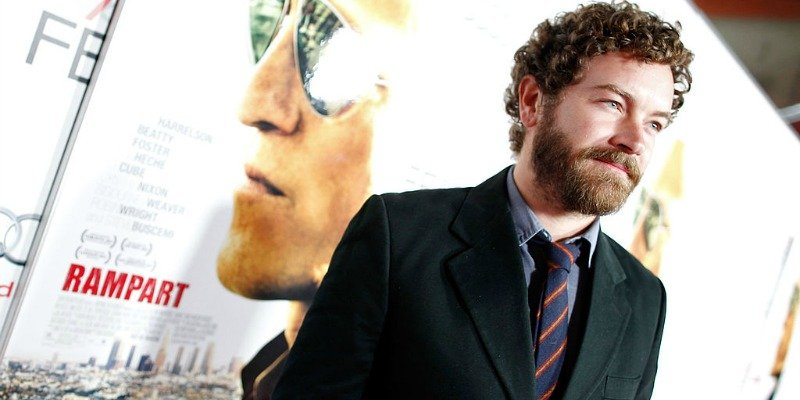 Danny Masterson stands in front of a Rampart poster