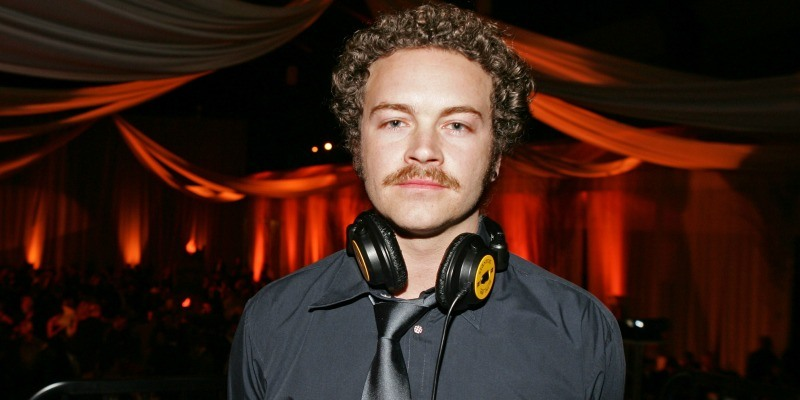 Danny Masterson stares into the camera with headphones around his neck