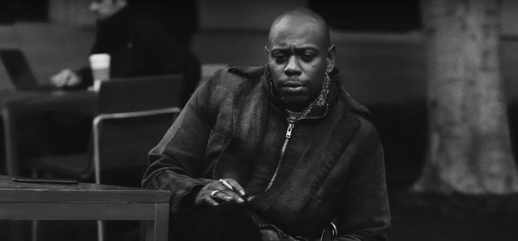 Dave Chappelle sits and smokes a cigarette, looking pensive