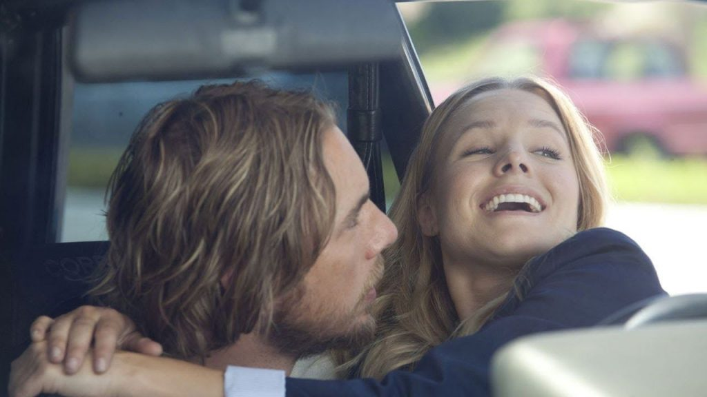 Dax Shepard leans in to kiss Kristen Bell in the front seat of a car