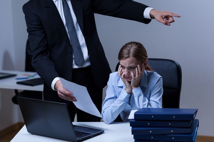 man holding paper in front of woman at desk