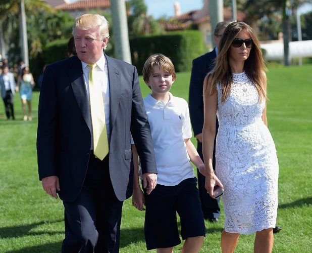 Donald Trump, Barron Trump and Melania Trump walking on a green lawn.