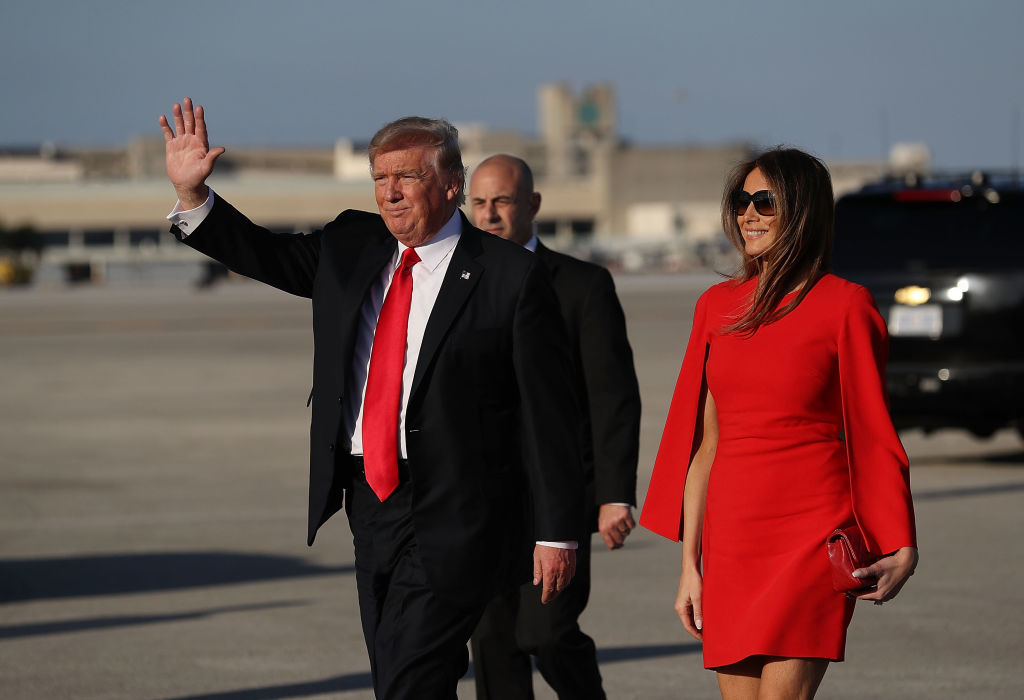 U.S. President Donald Trump walks with his wife Melania Trump.
