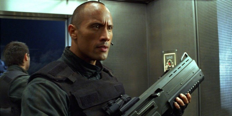 Dwayne Johnson is holding a large gun in Doom.