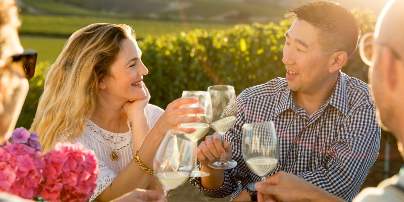 Drew Barrymore and winemaker, Kris Kato drinking wine in a vineyard.