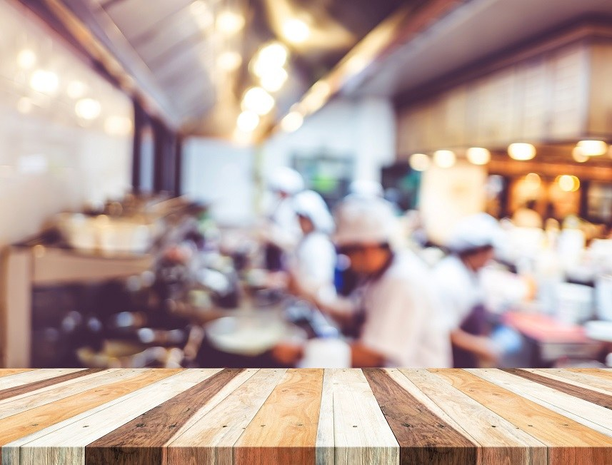 Wood table with blur open cooking restaurant