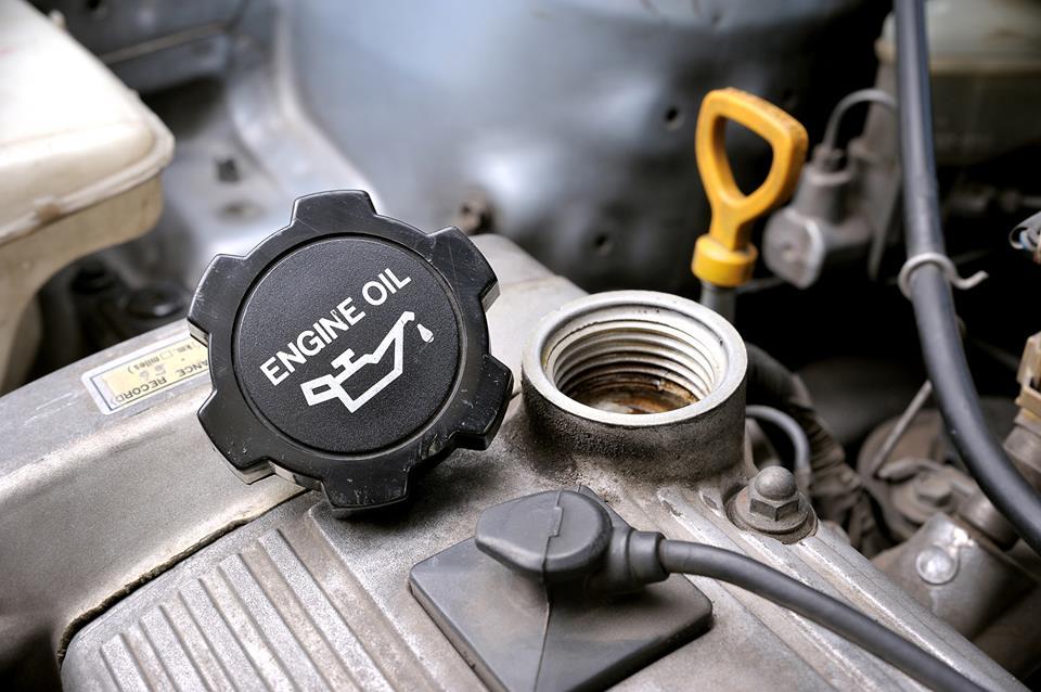 An unscrewed engine oil cap