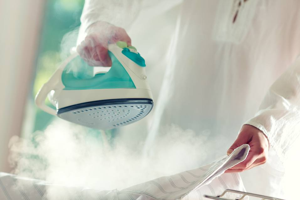 Woman's hands holding hot iron