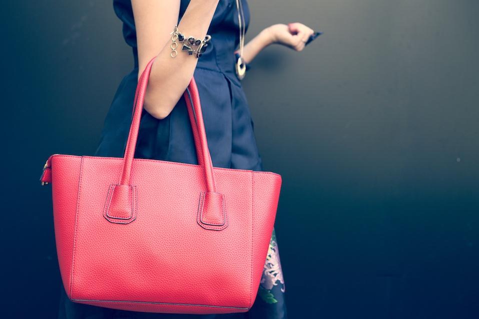 Fashionable beautiful big red handbag on the arm of the girl