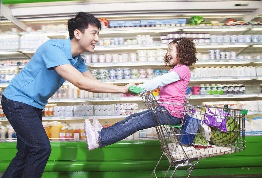 Father pushing daughter in shopping cart