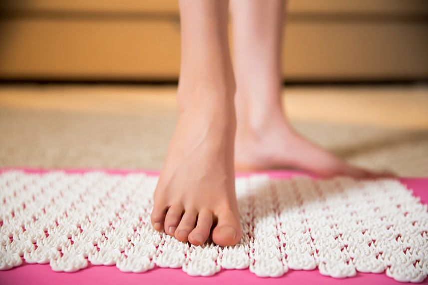 Female feet standing on acupressure mat
