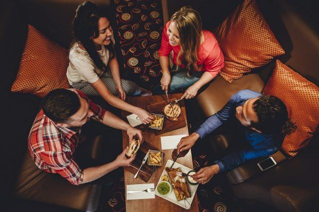 Overhead view of a group of friends having a meal at a restaurant. They are eating burgers and fish with chips.