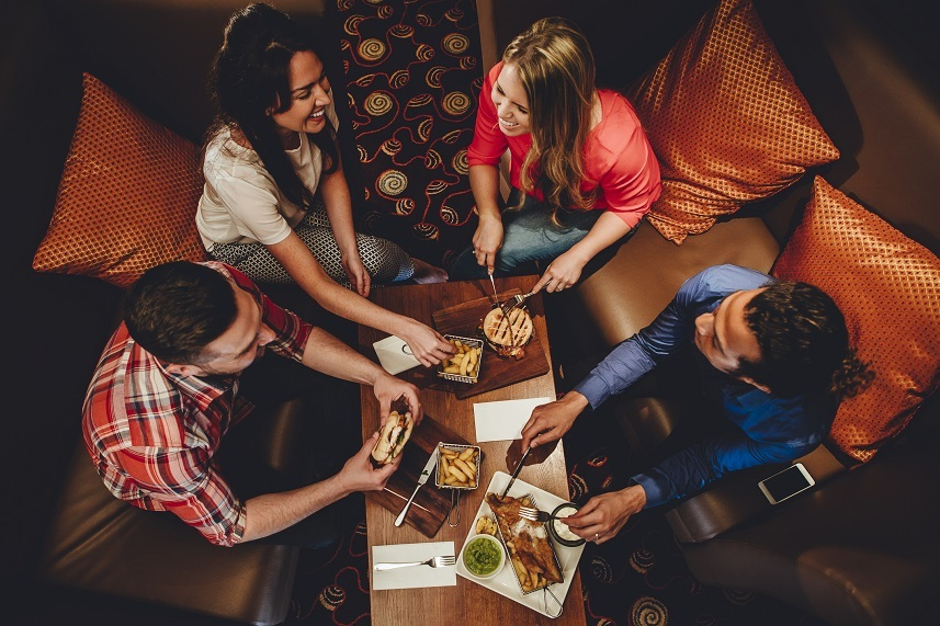 Overhead view of a group of friends having a meal at a restaurant.