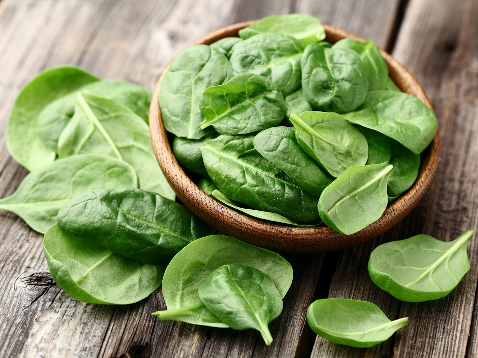 Spinach in and around a bowl on a wooden table.