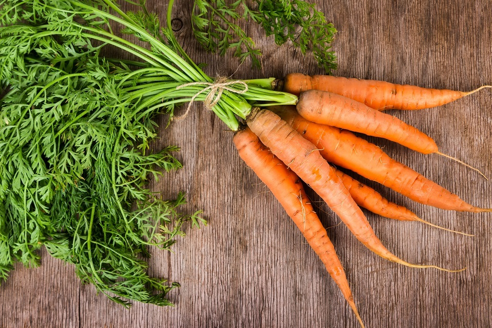 Fresh carrots arranged on a wooden background.