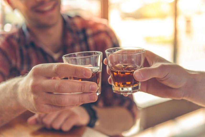 men clanging glasses of alcoholic beverage