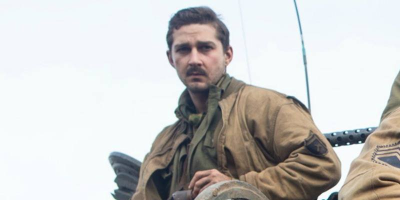 Shia LaBeouf posing in Fury in a tan jacket with a mustache
