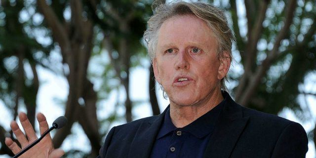 Gary Busey looking to the left of the frame with his mouth open.