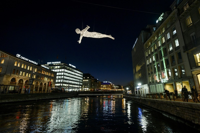 """One of """"The Travellers"""" created by French artist Cedric Le Borgne appears to fly above the Rhone in Geneva -- one of the world's most expensive cities"""