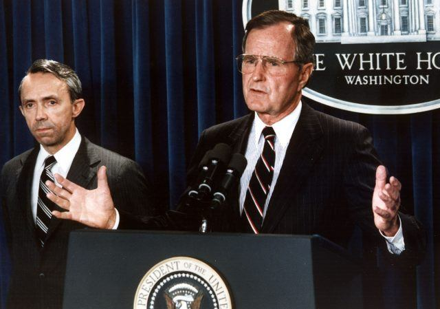 George H.W Bush speaking in front of a podium.