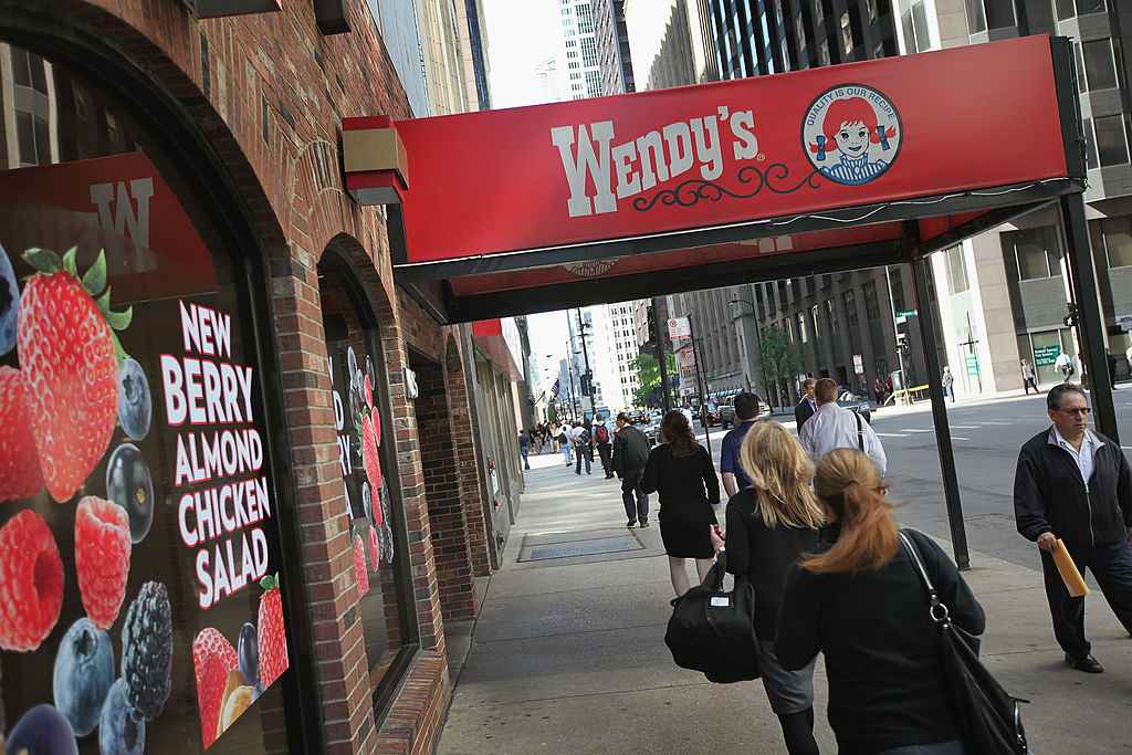 Pedestrians walk past a Wendy's restaurant