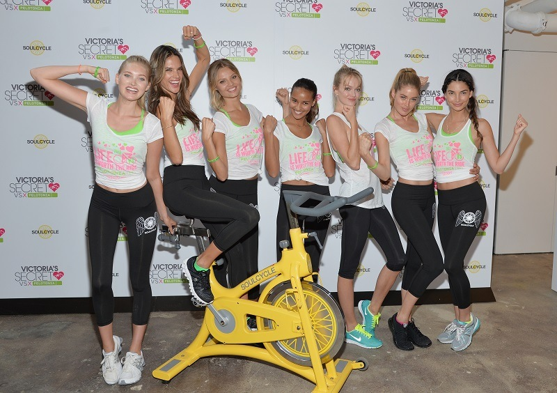 Models stand around a SoulCycle cycle