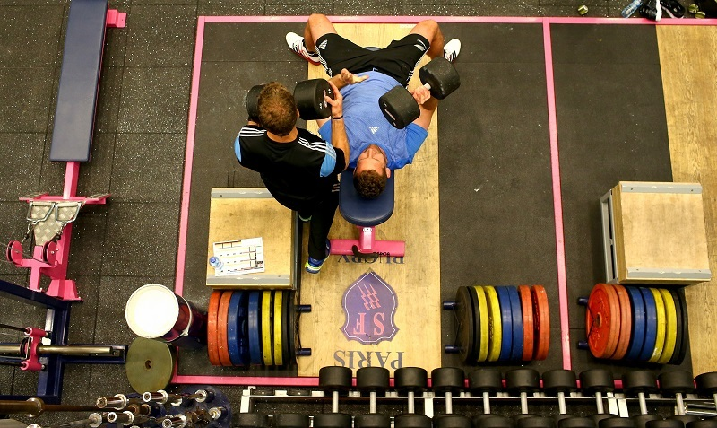 A man works out with a trainer in a gym