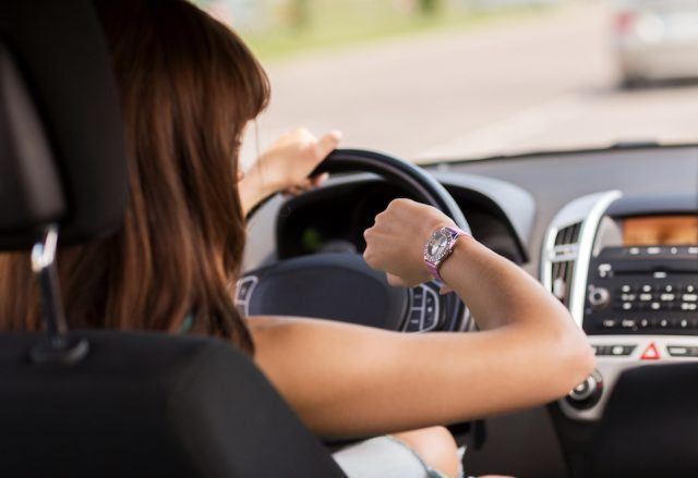 A woman checks her watch while driving on the road.