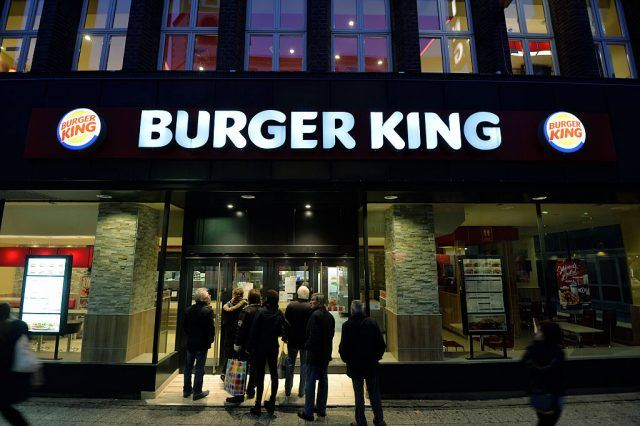 A group of people stand in front of Burger King's doors.