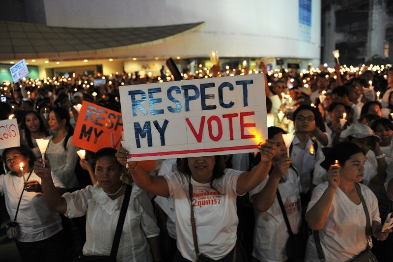 Pro-election democracy activists take part in a candlelight vigil backing democratic government in Bangkok.