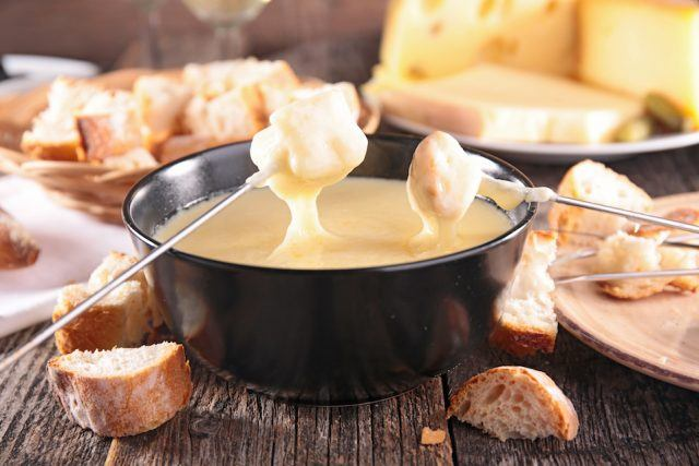 Dipping bread into a bowl filled with cheese fondue.