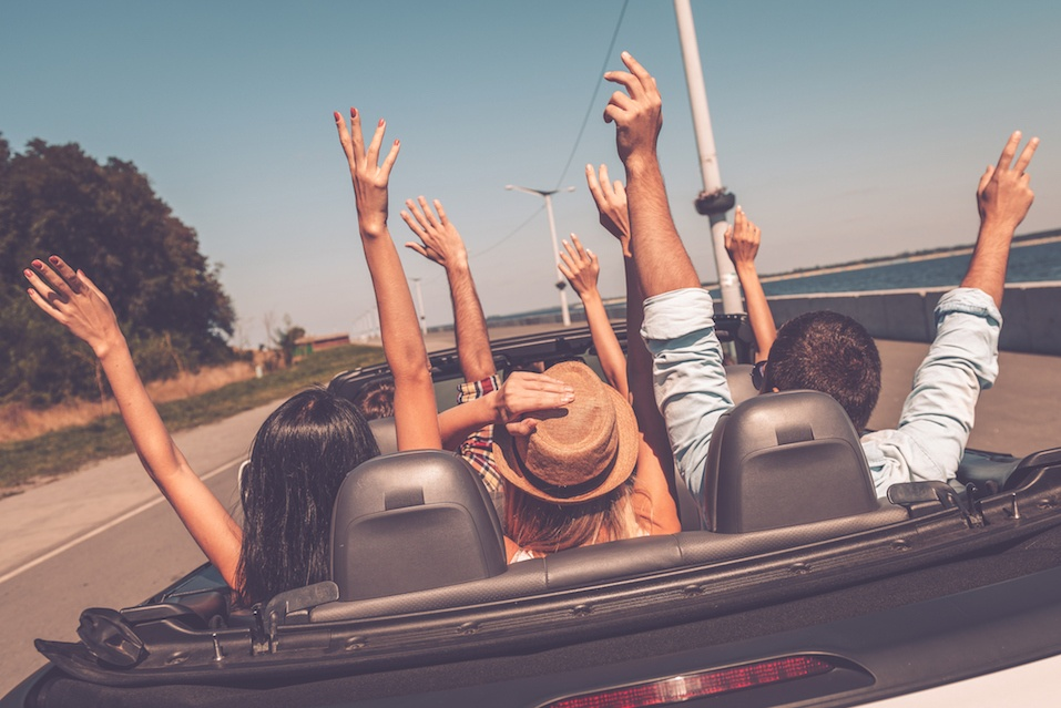 Young happy people enjoying road trip in their convertible and raising their arms up