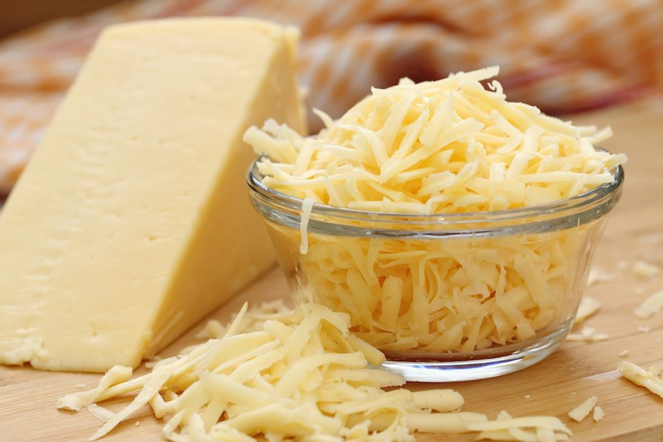 Glass bowl filled with grated cheese next to a wedge of cheese on a table.