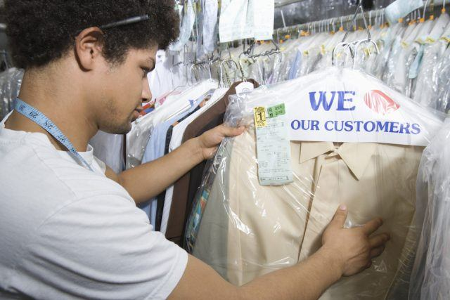 Young man working in dry cleaners.